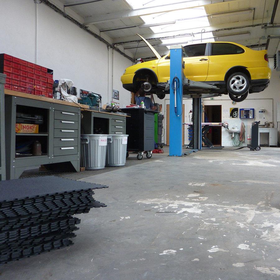 Plastové dlaždice Fortelock Industry - pokládka nové podlahy v autoservise - černá barva, dezén kůže.