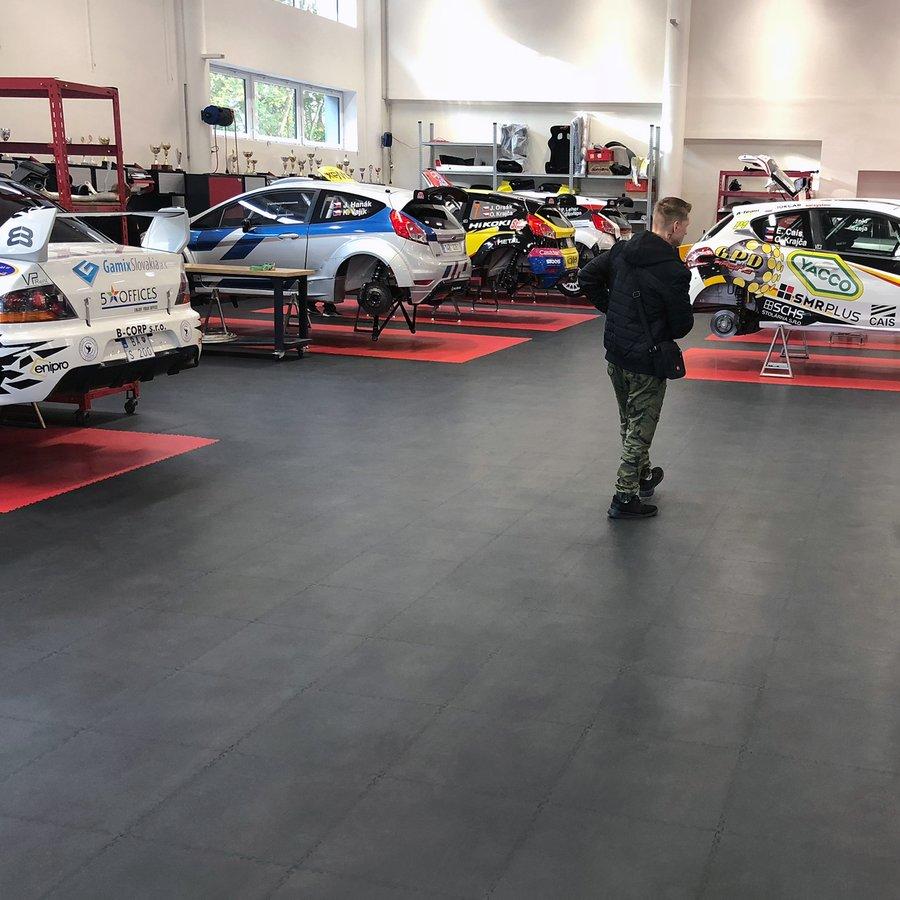 Plastové dlaždice Fortelock Industry - PVC podlaha v dílně rally týmu - kombinace černé a červené barvy, dezén kůže.